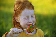 Portrait of happy girl eating a lollipop - GAF00116