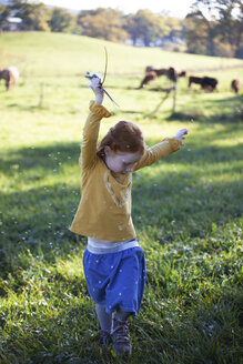 Redheaded girl dancing in field with blowball - GAF00125