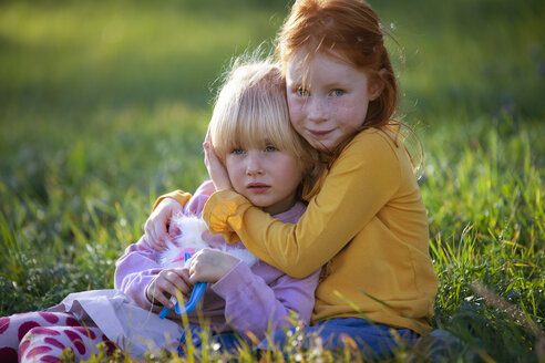 Portrait of girl hugging her sister in field - GAF00128