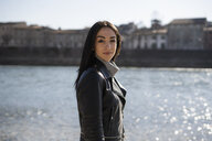Italy, Verona, portrait of smiling young woman at the riverside - GIOF05961
