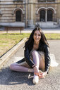 Italy, Verona, portrait of smiling young woman sitting down wearing leather jacket and tutu - GIOF05964