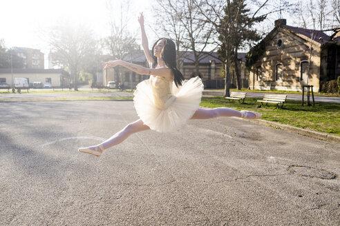 Italy, Verona, Ballerina dancing in the city jumping midair - GIOF05982