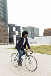 Spain, Barcelona, businessman riding bicycle in the city - VABF02251
