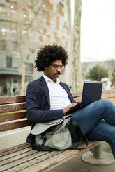 Spain, Barcelona, businessman in the city sitting on bench using laptop - VABF02281