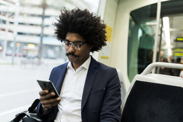 Spain, Barcelona, businessman in a tram using cell phone - VABF02302