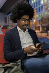Spain, Barcelona, businessman in a tram at night using cell phone - VABF02326