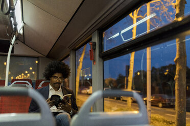 Spain, Barcelona, businessman in a tram at night reading a book - VABF02329