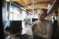 Focused businesswoman using computer in office - HEROF33117