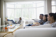Family watching TV on living room sofa - HEROF33141