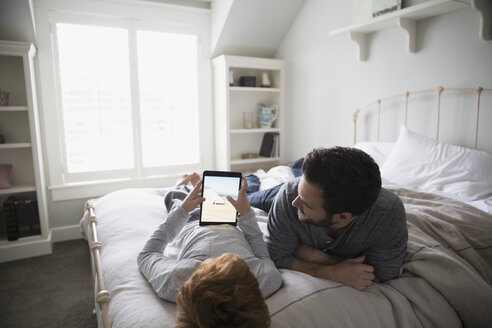 Father and son using digital tablet on bed - HEROF33177