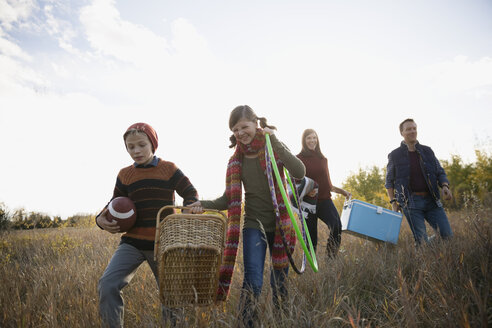 Family carrying picnic supplies in field - HEROF33240