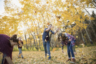 Family playing throwing autumn leaves - HEROF33252