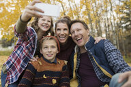 Family taking selfie in autumn park - HEROF33255