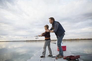 Father teaching son fishing on lake jetty - HEROF33261