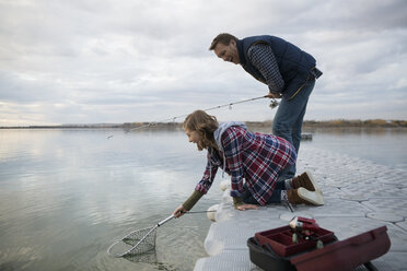 Father and daughter catching fish with net on lake jetty - HEROF33267
