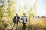 Couple running in sunny field - HEROF33273