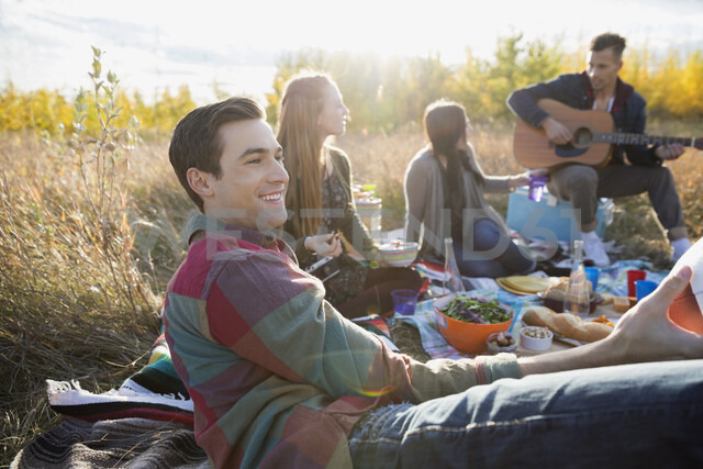 Friends hanging out enjoying picnic in sunny field - HEROF33282 - Hero Images/Westend61