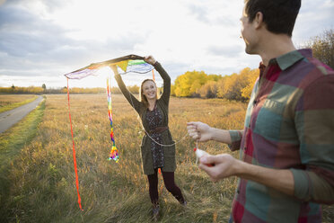 Couple flying a kite in autumn field - HEROF33288