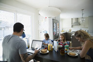 Family using cell phones and laptop breakfast table - HEROF33297