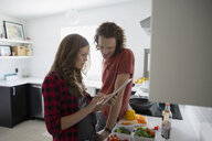 Couple with digital tablet cooking in kitchen - HEROF33315