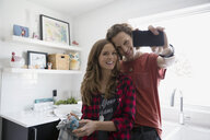 Couple taking selfie in kitchen - HEROF33318