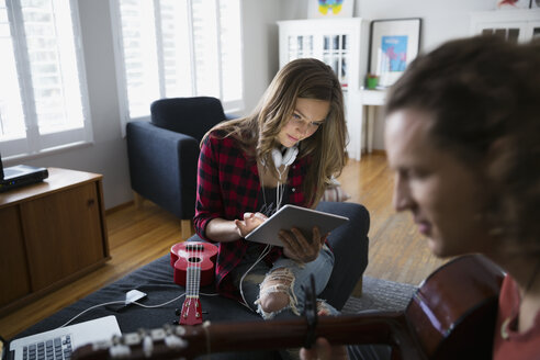 Couple with guitar and ukulele using digital tablet - HEROF33327