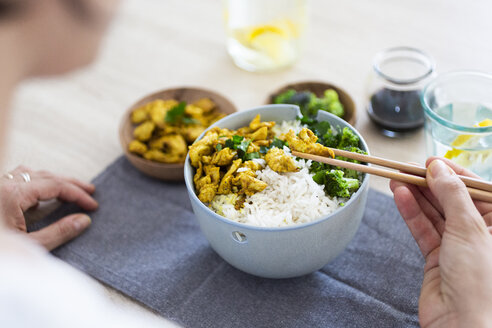 Curry chicken, broccoli and rice, woman with chopsticks - GIOF06009