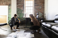 Creative business people reviewing proofs on office floor - HEROF33363