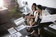 Creative businesswomen reviewing proofs on sofa in office - HEROF33570