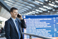 Smiling businessman on cell phone at the station - DIGF06416