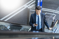 Businessman with suitcase and cell phone on escalator - DIGF06419