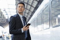 Businessman with cell phone on station platform - DIGF06422