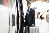 Businessman with suitcase getting in train - DIGF06425