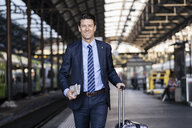 Smiling businessman walking with suitcase on station platform - DIGF06428