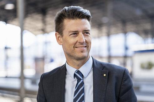 Portrait of smiling businessman at station platform - DIGF06437