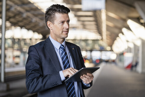 Businessman using tablet at train station - DIGF06440