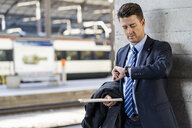 Businessman checking the time at train station - DIGF06446