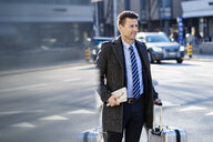 Businessman with suitcase at the street in the city - DIGF06464