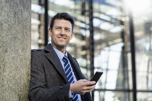 Smiling businessman with cell phone leaning against a wall - DIGF06470