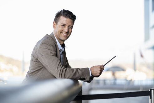 Smiling businessman with tablet standing outdoors - DIGF06482