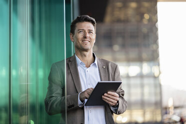 Smiling businessman using tablet outdoors - DIGF06485