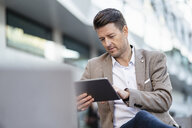 Businessman using tablet outdoors - DIGF06494