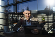 Businessman using tablet behind the window in a cafe - DIGF06500
