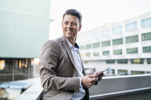 Smiling businessman with tablet on balcony in the city - DIGF06515