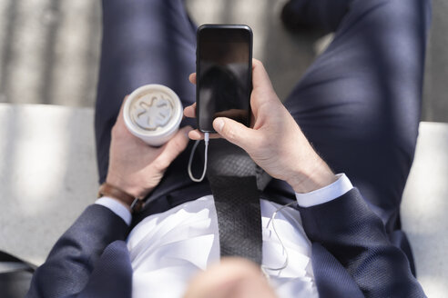 Close-up of businessman with takeaway coffee and smartphone outdoor - FMOF00508