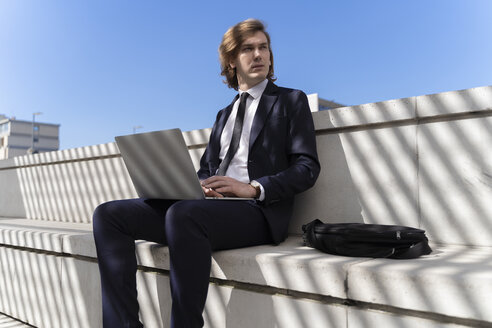 Italy, Florence, young businessman using laptop outdoor - FMOF00511