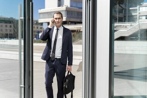 Italy, Florence, young businessman on smartphone outdoor - FMOF00517