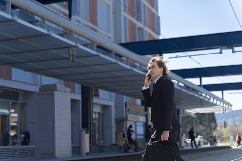 Italy, Florence, young businessman on smartphone outdoor - FMOF00520