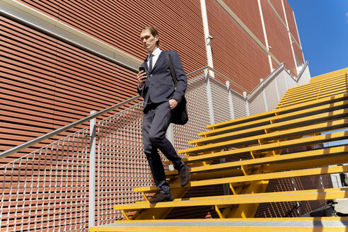 Italy, Florence, young businessman with ear buds using smartphone outdoor - FMOF00532
