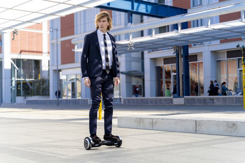 Italy, Florence, young businessman riding hoverboard in the city - FMOF00535